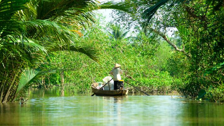 Une embarcation remontant les eaux du Mékong, dans la jungle Cambodgienne