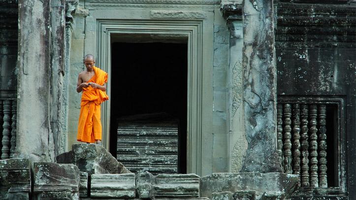 Un moine visitant Angkor Wat